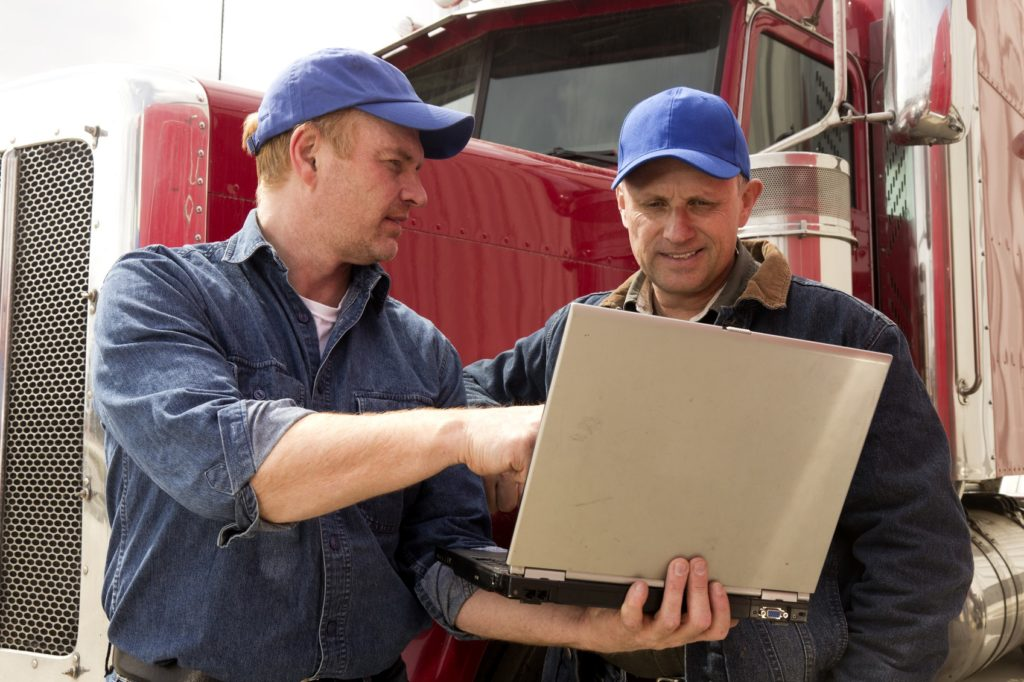 Commercial moving industry two truck drivers in conversation while using a laptop computer.